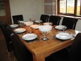 The large oak dining table seats 8 people, extending to accommodate 10.